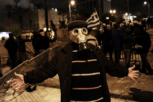 A protester wearing a gas mask poses for