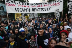Women hold up a banner reading 'Equal rights for all refugees' as they participate with their children in a demonstration by in Greece stranded refugees and supporting groups in Athens on March 30, 2016. Currently some 53,000 refugees and migrants are stranded in Greece, compared to 30,000 in late February before Balkan states began shutting their borders. / AFP PHOTO / LOUISA GOULIAMAKI